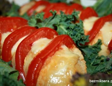 Bagietka z pomidorami i mozzarellą wśród jarmużowych liści.